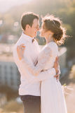 Newlyweds touch each other with noses on cityscape background Stock Photos