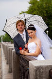 Newlyweds with umbrella Stock Photo
