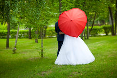 Newlyweds with umbrella in the shape of a heart Stock Photos