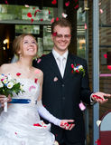 The newlyweds under the rose petals Royalty Free Stock Photography