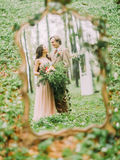The newlyweds in the vintage clothes in the full high looking at the each of other and their reflection in the mirror. The close-up photo in the forest stock photos