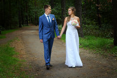 Newlyweds walking along the garden path holding hands. Newly married couple walk on park paths holding hands and looking at each other Stock Image