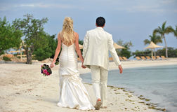 Newlyweds walking on beach together Stock Image