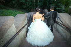 Newlyweds walking down stone stairs Royalty Free Stock Photography