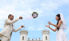 Newlyweds walking. Bride and groom funs and frolics with wedding bouquet.  Newlywed couple walk around the ancient palace near Sharovka town, Kharkiv region Royalty Free Stock Images
