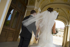 The newlyweds are walking under church  arches. Stock Photos