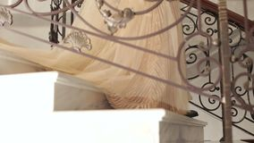 Newlyweds in wedding attire down the stairs, close-up. A beautiful young couple in an evening dress and costume descends a chic vintage staircase. Newlyweds in stock footage
