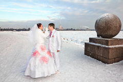 Newlyweds in wedding attire with glasses amid a winter of St. Petersburg at strelka of vasilievsky island Royalty Free Stock Image