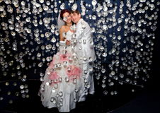 Newlyweds in wedding attire posing in scenery of glass balls Royalty Free Stock Images