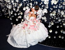 Newlyweds in wedding attire posing in scenery of glass balls Royalty Free Stock Photography