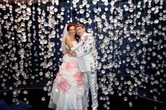 Newlyweds in wedding attire posing in scenery of glass balls Stock Image
