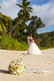 Newlyweds with wedding bouquet. Of jasmine on the beach in the Seychelles Royalty Free Stock Photos