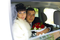 Newlyweds in wedding car Stock Images