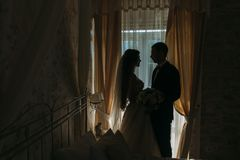 Newlyweds at wedding day. happy luxury bride and groom standing at window light in rich room, tender moment. Newlyweds at wedding day. happy luxury bride and Royalty Free Stock Images