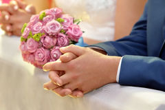 Newlyweds with wedding rose bouquet at the church Stock Images