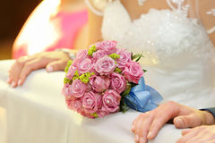 Newlyweds with wedding rose bouquet at the church Royalty Free Stock Images