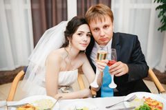 Newlyweds at the wedding table sitting together Royalty Free Stock Images