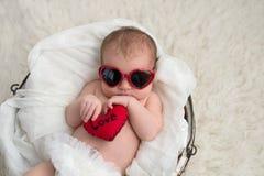 Newobrn有心形的太阳镜的女婴 免版税库存照片