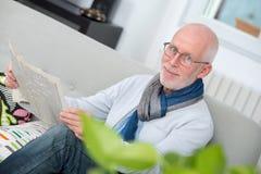 Newpaper mûr beau de lecture d'homme sur le sofa Images stock
