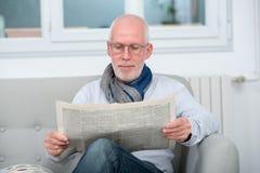 Newpaper mûr beau de lecture d'homme sur le sofa Photos libres de droits