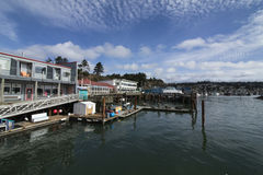 Newport Bayfront, Oregon. Bright shops and restaurants line the Yaquina Bay, framed by piers and docks. This is an area of tourism and fisheries royalty free stock photo