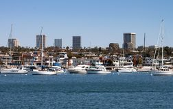 Newport Beach California harbor and city skyline. Boats yachts homes and Fashion Island high rise buildings in the background on a sunny day stock photography