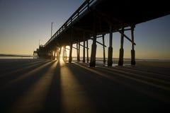 Newport Beach Pier 16506. The sun sets castinf long shadows behind the pier at Newport Beach, California, USA stock photo