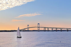 Newport Bridge Sailboat at Twilight Rhode Island. Sunset with Newport Bridge and sailboats Newport, Rhode Island, USA. The person in the sailboat is in