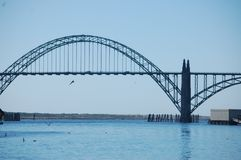 Newport, Oregon`s Historic Yaquina Bay Bridge. Birds fly around Newport, Oregon`s historic Yaquina Bay Bridge under a clear blue sky stock images
