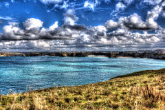 Newquay coast Cornwall UK with white clouds and blue sky in bright colourful HDR Stock Image