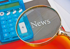 News. The word news on a magazine cover photographed close-up beside an electronic calculator to cover the concept of financial news all viewed though a stock photo