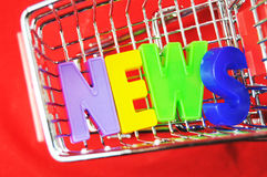 News. The word 'News' made by plastic letters in a shopping trolley against red background Stock Images