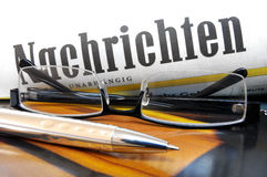 News. Paper with lettering  in German language plus glasses and ball point Stock Photos
