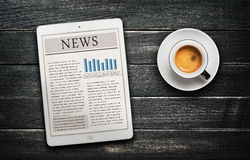 News article on digital tablet and coffee cup Royalty Free Stock Images