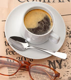 News and coffeecup. Coffee cup and glasses on a financial newspaper Royalty Free Stock Images