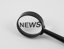 News concept. Isolated on white: sign NEWS through magnifying glass on the white background Royalty Free Stock Images