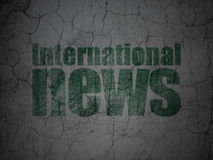 News concept: International News on grunge wall background. News concept: Green International News on grunge textured concrete wall background Royalty Free Stock Photos