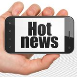 News concept: Hand Holding Smartphone with Hot News on display. News concept: Hand Holding Smartphone with black text Hot News on display, 3D rendering royalty free stock photography