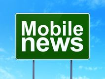 News concept: Mobile News on road sign background Royalty Free Stock Photos