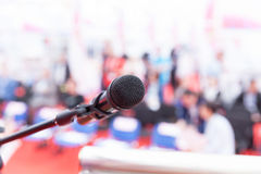 News conference. Microphone in focus against blurred audience. Royalty Free Stock Photo