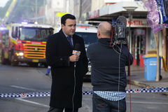 News correspondent delivers a news bulletin live. ROZELLE, AUSTRALIA - SEPTEMBER 4, 2014; News correspondent delivers a news bulletin on site of shop blast live Stock Photo
