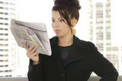 Daily News & Finance. Woman reads the finance pages