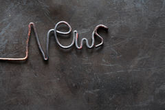 News Inscription. Periodical Press concept. Word News made from metal wire on grange dark background Stock Images