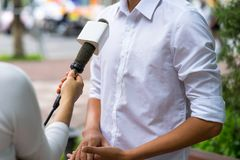 News journalist with microphone interviewing on street closeup.  Stock Photo