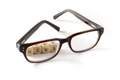 News message written in wooden blocks behind glasses, isolated o Royalty Free Stock Photo