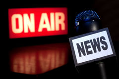 News Microphone On-Air. A Microphone with the word News on the side and on-air radio and television broadcast sign in the background with copy space Royalty Free Stock Images