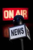 News Microphone On-Air Vertical. A Microphone with the word News on the side and on-air radio and television broadcast sign in the background with copy space Stock Photo