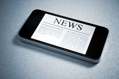 News On Mobile Smartphone. Modern mobile phone lying down on table with fresh news on screen. Added a slight vignetting and toning color for dramatic effect and Stock Photo