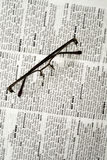 News, newspaper. Eyeglasses on newspaper page stock photo