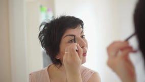Girl paints eyebrow makeup. News presenter paints eyebrow makeup stock video